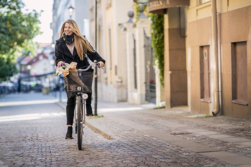 Kvinna cyklar på klassisk damcykel i centrala Örebro