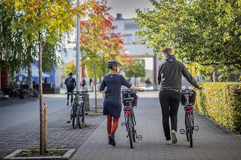 Två personer leder cyklar på campus Örebro